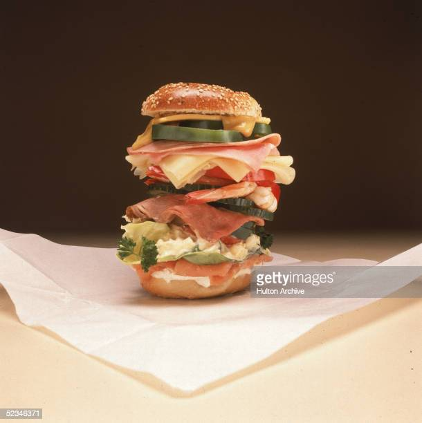 A multilayered bagel sandwich includes cream cheese lox lettuce egg salad parsley green peppers tomato roast beef cucmber shrimp cheese ham and...