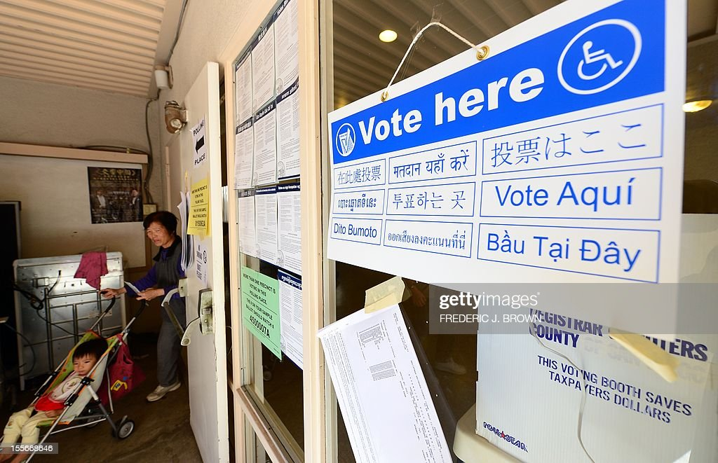A multilingual 'Vote here' sign is displayed as a woman pushes a stroller out of the voting room at Christ Lutheran Church in Monterey Park, Los Angeles County, on November 6, 2012 in California, as Americans flock to the polls nationwide to decide between President Barack Obama, his Rebuplican challenger Mitt Romney, and a wide range of other issues. Monterey Park is one of six cities in California's 49th Assembly District, the state's first legislative district where Asian-Americans make up the majority of the population. AFP PHOTO/Frederic J. BROWN