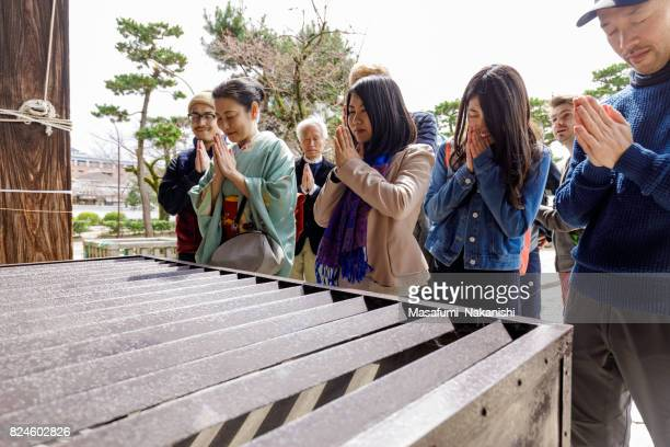 Multinational people praying in Japanese temples