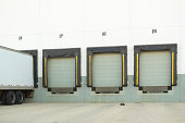 Photo of 3 empty shipping dock doors and one with a truck parked (landscape).  Photos take in relation to shipping and receiving, warehouse, and transportation.