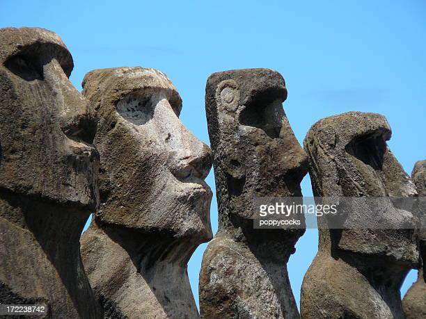 Multiple Easter island heads against a blue background