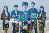 Multiple exposure of group of businessperson and modern cityscape.
