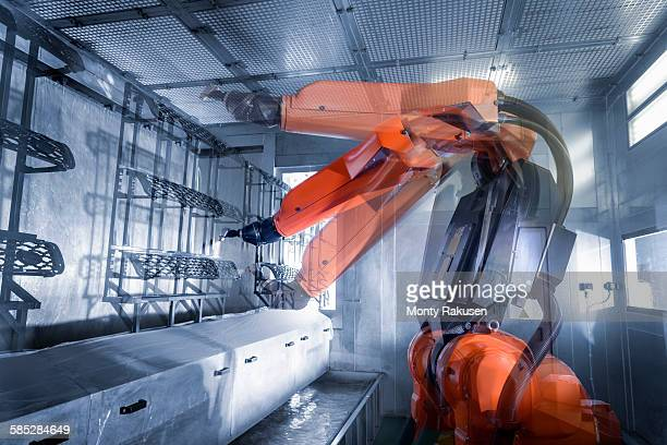 Multiple exposure of robot spray painting automotive parts in spray paint factory, close up