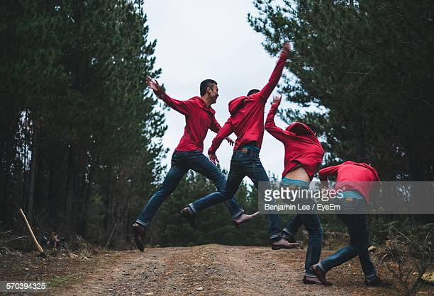 Multiple Exposure Of Young Man Jumping On Dirt Road In Forest