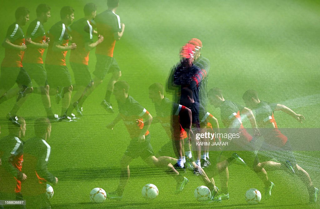 A multiple exposure picture shows Paris Saint-Germain's (PSG) football players and the team's Italian coach Carlo Ancelotti (C) taking part in a training session at the Aspire Academy of Sports Excellence in the Qatari capital Doha on December 30, 2012. PSG is in Qatar for a week-long training camp before the resumption of the French Ligue 1 after the winter break.
