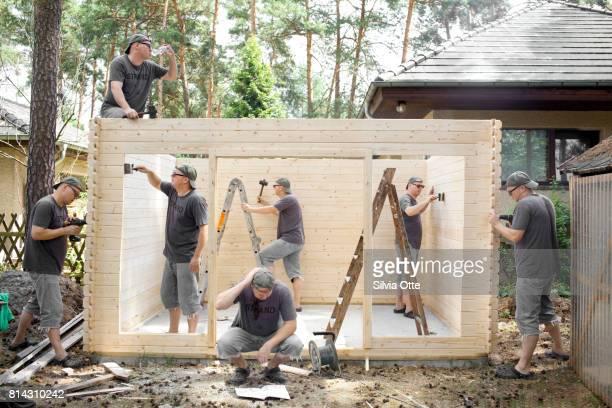 Multiple Exposures of man building wooden shack