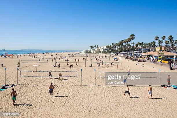 Multiple games of beach volleyball at Huntington Beach, California