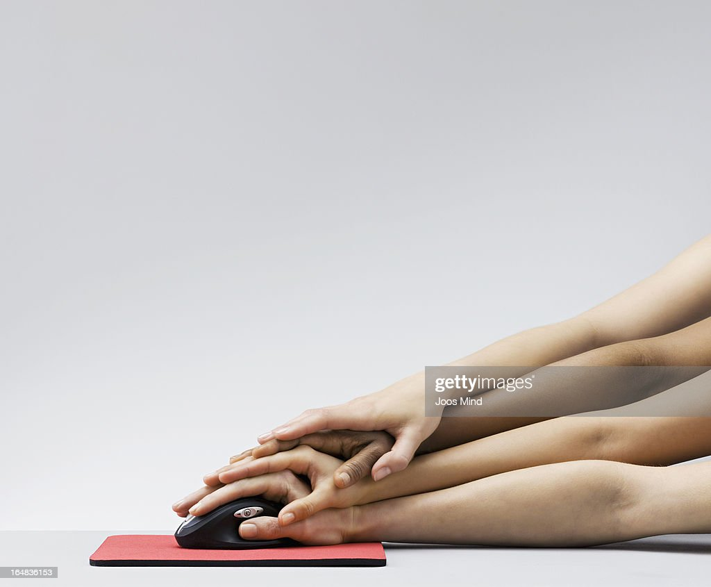 Multiple hands all clicking on a mouse