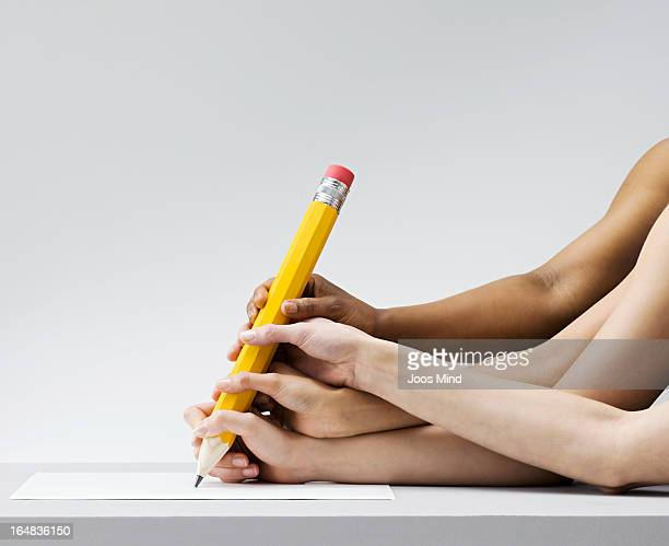 Multiple hands all writing with one pen