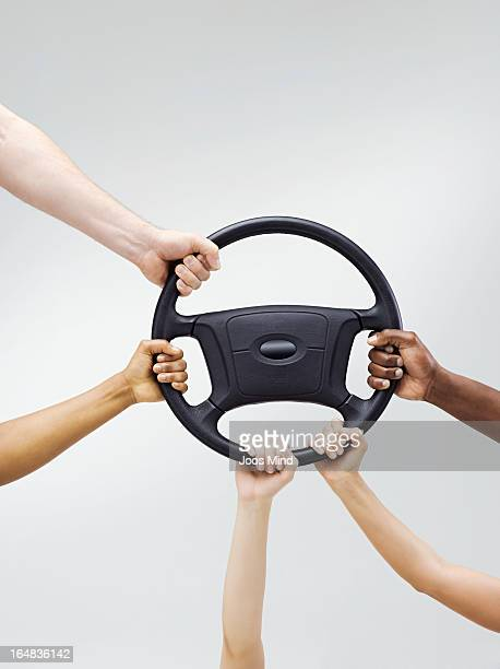 Multiple hands holding a car steering wheel