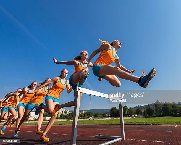 Multiple image of female hurdler jumping over hurdle