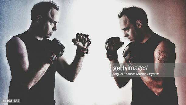 Multiple image of mid adult man boxing against wall