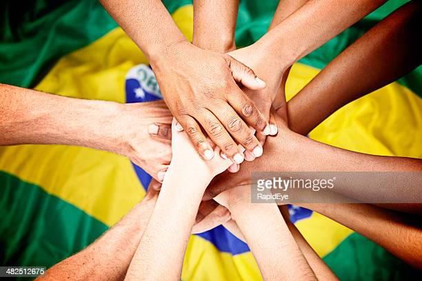 Multiple mixed hands pile onto Brazilian flag pledging loyalty