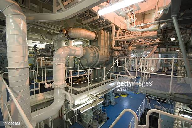 Multiple pipes leading in multiple directions in engine room