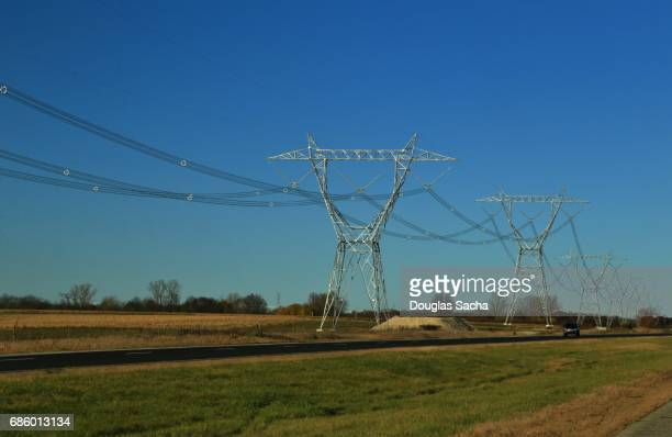 Multiple power lines on overhead towers running along a rural highway