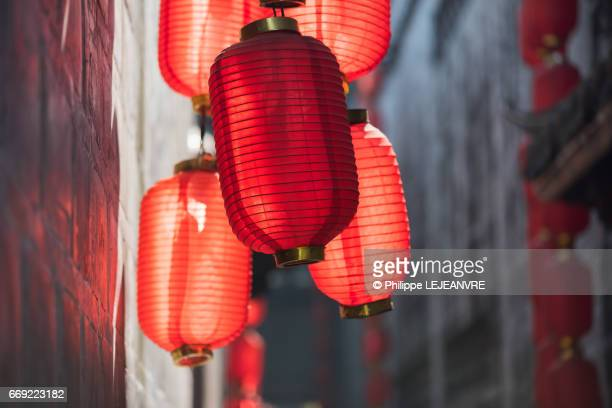 multiple red chinese lanterns in sunlight in a narrow street