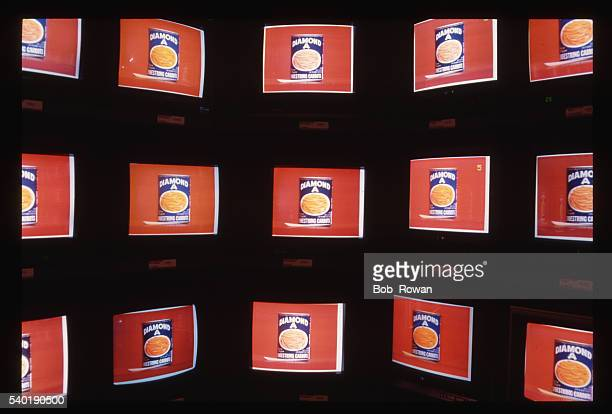 Multiple television monitors line a display wall inside a video store