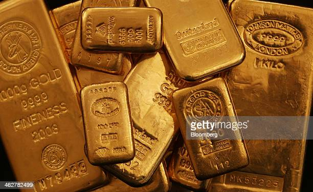 Multiple weighted gold bars sit in a stack in this arranged photograph at Gold Investments Ltd bullion dealers in London UK on Wednesday Jan 15 2014...