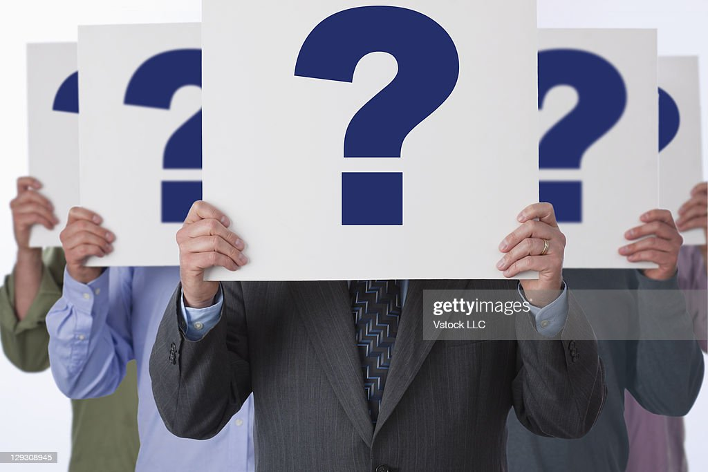 Multiplied businessman standing with question marks in fron of his face