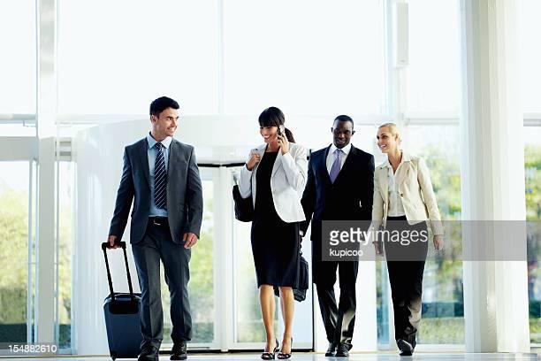 Rassen business Personen mit Gepäck zu Fuß auf dem Flughafen