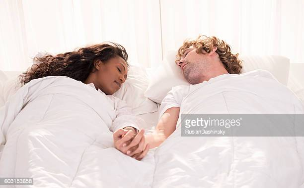 Multiracial calm couple sleeping together.