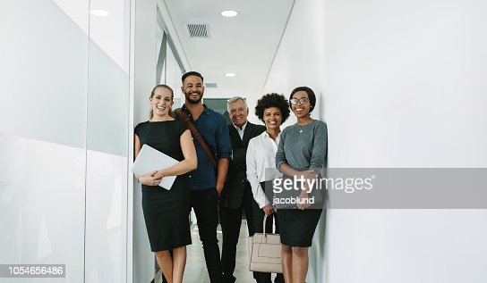 Multiracial corporate professionals in office hallway : Stock Photo