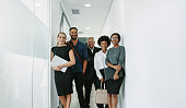Portrait of happy business group standing together in office corridor. Multiracial business professional in office hallway.