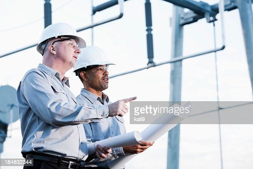 Multiracial engineers at industrial site looking up