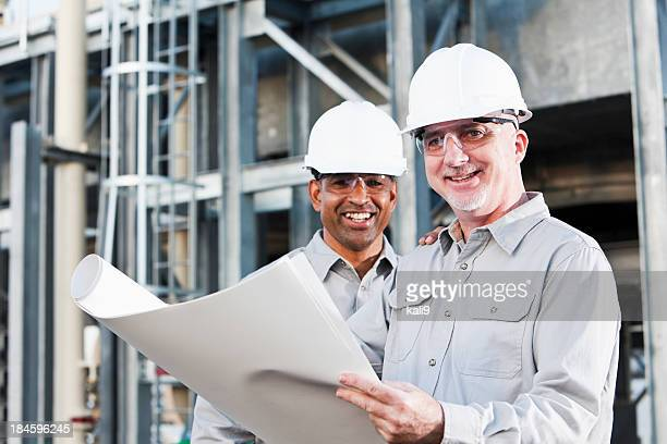 Multiracial engineers at industrial site reading plans