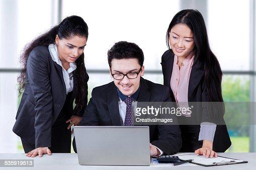 Multiracial entrepreneurs using laptop : Stock Photo