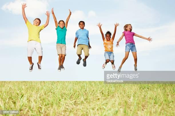 Rassen Freunde springen hoch in die Luft gegen Himmel
