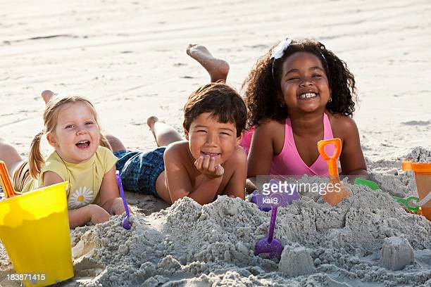 Multiracial friends playing in sand at the beach