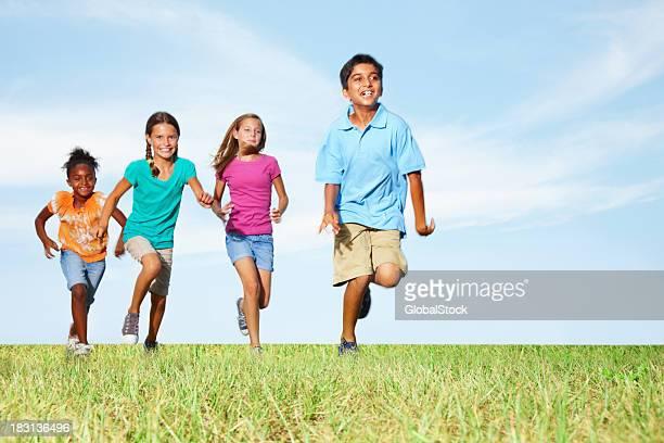 Multiracial friends running on grass against sky