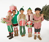 Multiracial group of children (5-7) dressed as elves, holding Christmas gifts and tree, portrait
