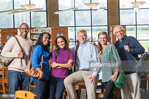 Groupe multi-ethnique des étudiants matures dans la bibliothèque