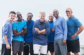 Diverse group of men wearing casual blue shirts, standing together outdoors.  Mixed ages, 20s to 70s.  They are confident and happy, smiling at the camera.
