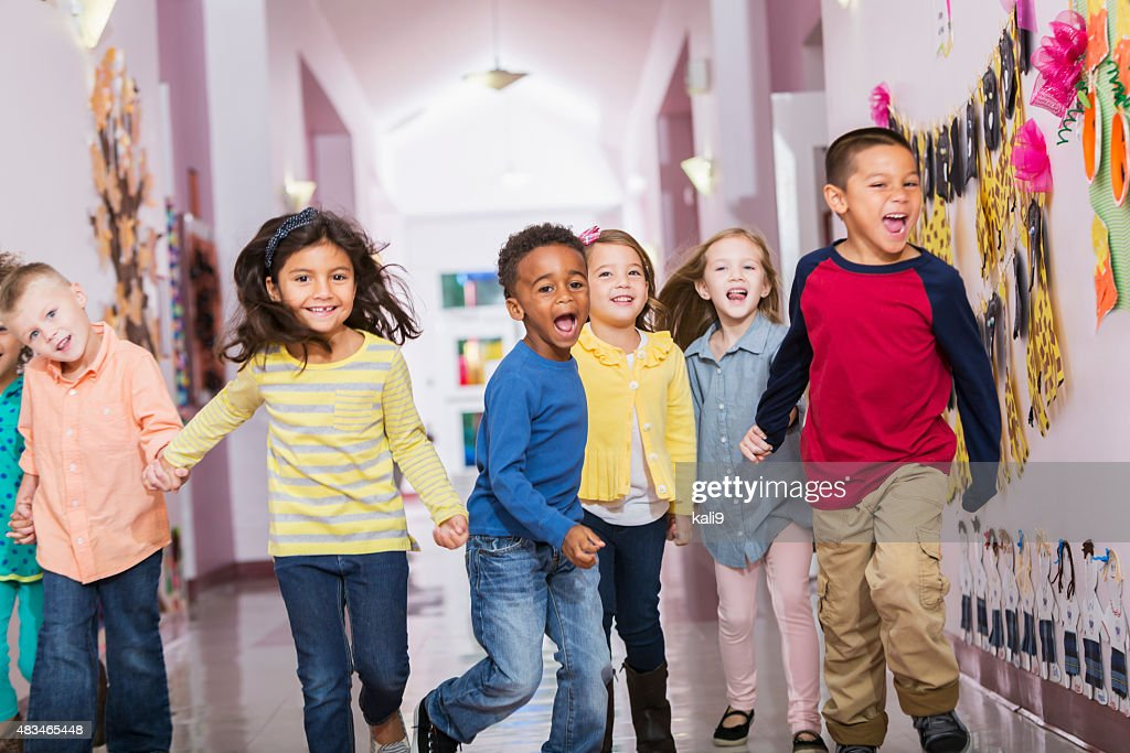 Multiracial group of preschoolers running down hallway : Stock Photo
