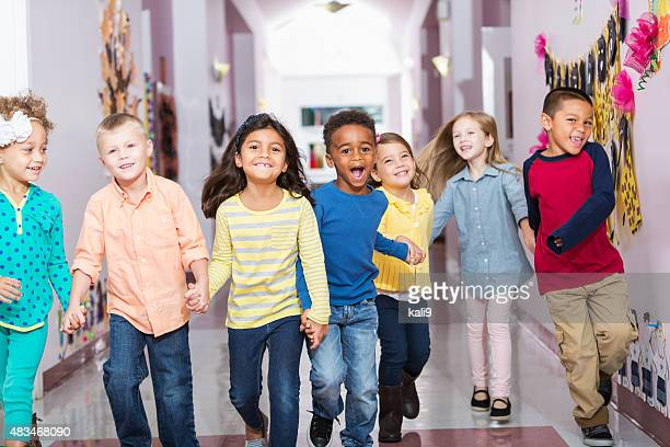 Multiracial group of preschoolers running down hallway