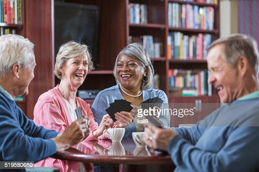 Multiracial group of seniors talking, playing card game