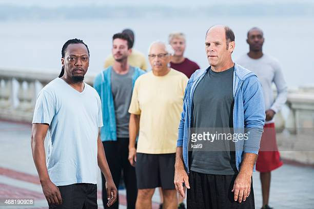 Multiracial group of serious men standing outdoors