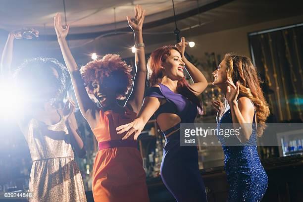 Multiracial group of women at a bar dancing
