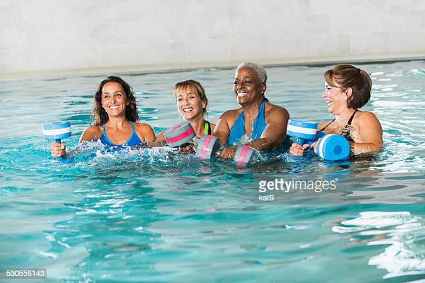 Multiracial group of women in water aerobics class
