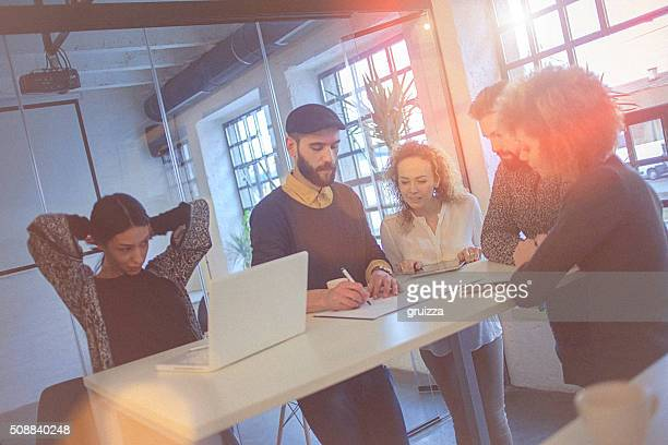Multiracial group of young entrepreneurs gathered around work schedule