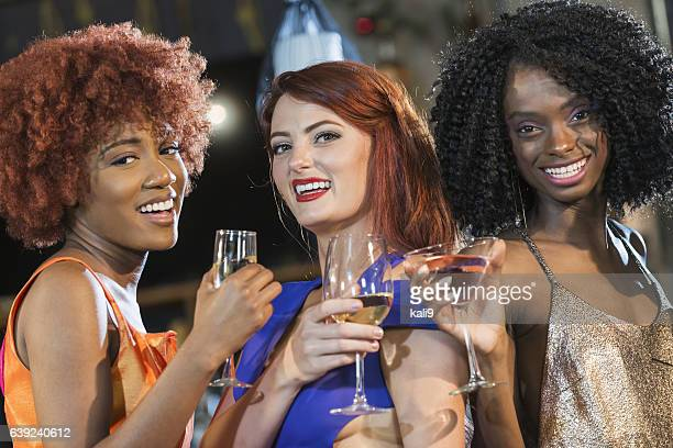 Multiracial group of young women drinking at bar