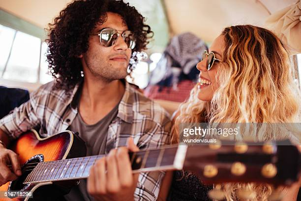 Multi-Racial Hipster friends Singing Together on road trip with guitar