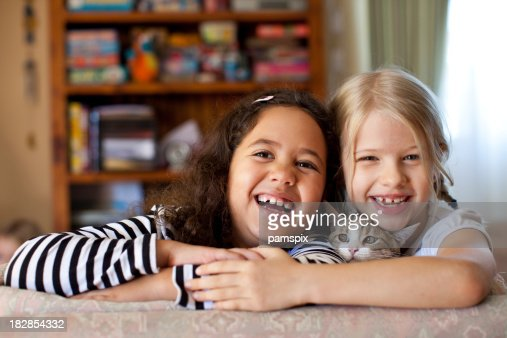 Multiracial Kids laughing indoors with pet kitten cat