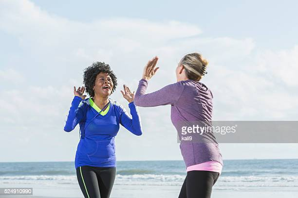 Multi-racial mature women, laughing and high fives