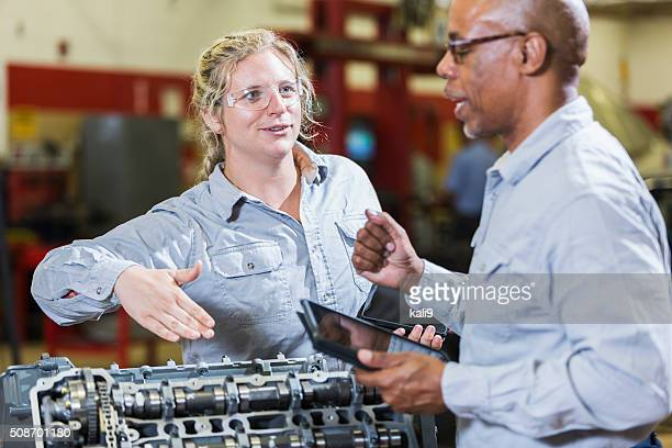 Multi-racial mechanics with engine and digital tablets