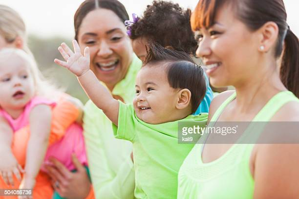 Multi-racial moms and babies, focus on Asian boy waving
