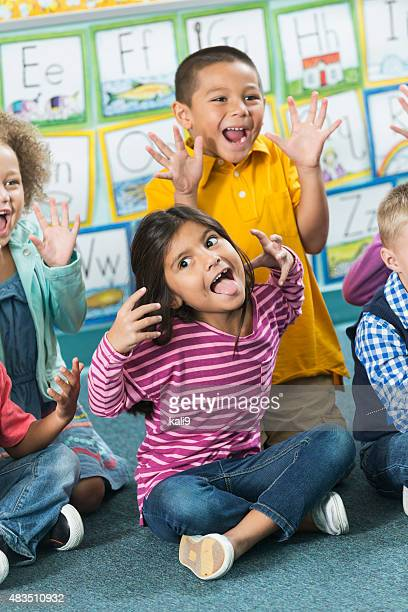 Multiracial preschoolers having fun making faces